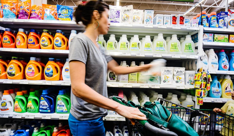 Consumirdora na seção de detergentes de um supermercado